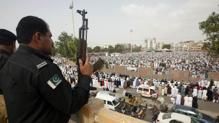 A policeman stands guard as Muslims say their Eid al-Fitr prayers in Karachi