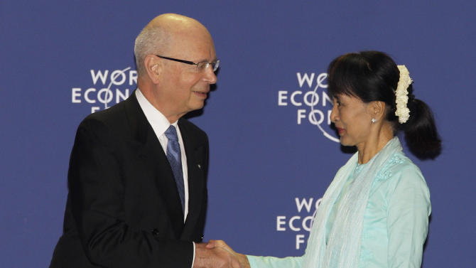 Myanmar opposition leader Aung San Suu Kyi, right, is welcomed by World Economic Forum Founder and Executive Chairman Klaus Schwab during the forum on East Asia in Bangkok, Thailand, Friday, June 1, 2012. (AP Photo/Sakchai Lalit)