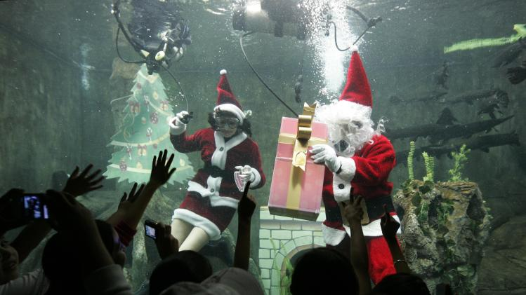 Divers dressed as Santa Claus swim in a fish tank as they greet children at the Guadalajara Aquarium in Zapopan