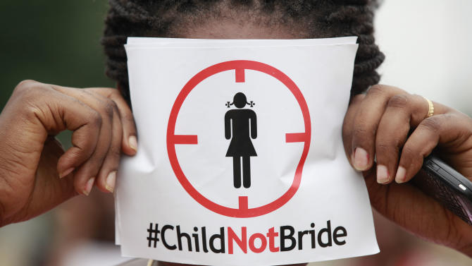 In this photo taken on Saturday, July 20, 2013, a woman protests against underage marriages in Lagos, Nigeria. Nigeria's secular and Islamic laws clashed when a senator notorious for marrying a 14-year-old filibustered a vote to amend the constitution by insisting that a girl child comes of age when she marries, not at 18. Enraged activists are demanding the senate revisit the vote, asking how a known pedophile could get away with subverting the country's constitution. (AP Photo/Sunday Alamba)