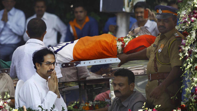 Udhav Thackeray, front left, the son of Hindu hardline Shiv Sena party leader Bal Thackeray, gestures next to his father's body during his funeral in Mumbai, India, Sunday, Nov. 18, 2012. Thackeray, the extremist leader linked to waves of mob violence against Muslims and migrant workers in India, died Saturday after an illness of several weeks. He was 86. (AP Photo/Rafiq Maqbool)