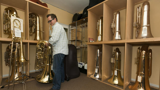 In this March 2, 2012 photo, The Horn Guys store manager/trumpet player Mike Davis moves new tubas inside the store, in La Crescenta, Calif. There's a Banda Bandit on the loose, some music directors say. Someone who is breaking into high schools from the East Side of Los Angeles to the shores of Manhattan Beach and stealing expensive tubas to supply a fast-growing banda black market.(AP Photo/Damian Dovarganes)