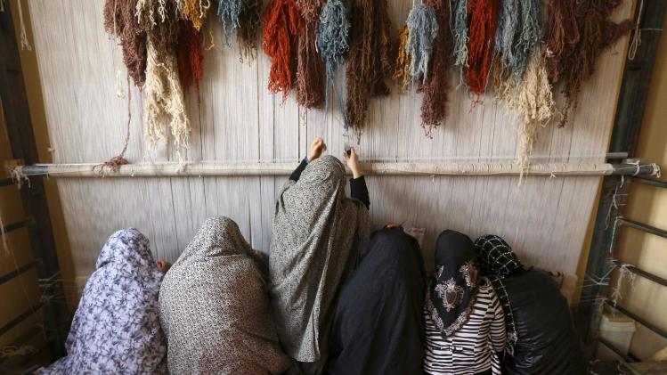 Afghan female prisoners weave a carpet at a workshop in Herat prison, western Afghanistan