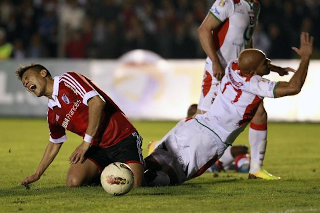 River Plate's Teofilo Gutierrez of Argentina, left, cries out after colliding with Liga Deportiva Universitaria de Loja's Jimmy Bermudez of Ecuador, in their battle for control of the ball during a Co