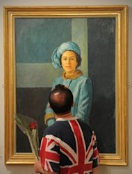 A visitor looks at a portrait of Queen Elizabeth II by British artist Michael Noakes at the Mall Galleries in London on May 2. A new exhibition at the National Portrait Gallery explores many facets of a queen who, after six decades on the throne, is still something of a mystery