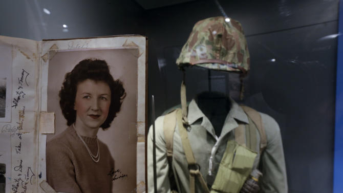 "In this May 23, 2013 photo, a page of out of the diary of 22-year-old Marine Cpl. Thomas Jones featuring a photo of his high school sweetheart, Laura Mae Davis Burlingame, is on display at the National WWII Museum in New Orleans. Behind is a Marine uniform like one Jones, who died in the bloody assault on a Japanese-held island during World War II, would have worn. Before Jones died, he wrote what he called his ""last life request"" to anyone who might find his diary: Please give it to Laura Mae Davis, the girl he loved. Laura Mae Davis Burlingame _ she married an Army Air Corps man in 1945 _  had given the diary to Jones, and didn't know it had survived him until visiting the museum on April 24. (AP Photo/Gerald Herbert)"