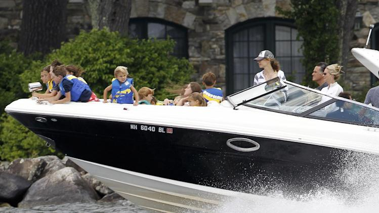 "FILE - In this July 5, 2012, photo Republican presidential candidate Mitt Romney, at right next to his wife Ann, drives his boat out of his vacation home with his grandchildren seated on the bow on Lake Winnipesaukee in Wolfeboro, N.H. Romney's large family is at the center of his life _ and of his presidential campaign. At a time when nontraditional families have become the norm _ and when even the Romneys are watching ""Modern Family,"" a popular sitcom that centers on unconventional family arrangements _ the Romney brood stands out. (AP Photo/Charles Dharapak, File)"