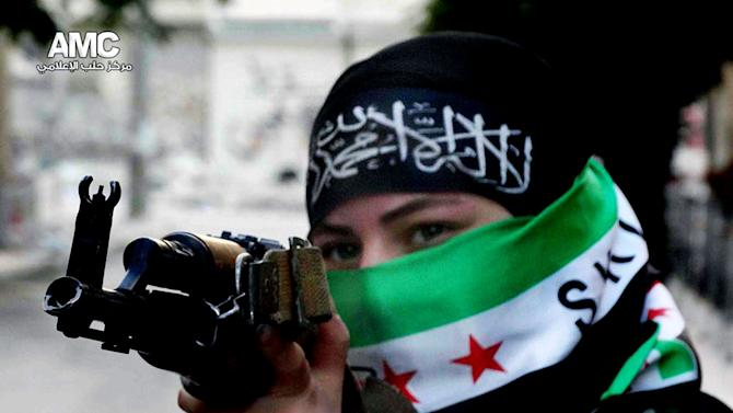 This Tuesday, June 25, 2013 citizen journalism image provided by Aleppo Media Center AMC which has been authenticated based on its contents and other AP reporting, shows a female Free Syrian Army fighter aiming her weapon, in Aleppo, Syria. (AP Photo/Aleppo Media Center AMC)