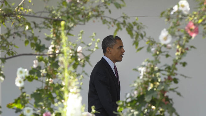 President Barack Obama walks along the Colonnade at the White House in Washington, Friday, June 15, 2012, before heading to Chicago for the weekend with his family. (AP Photo/Susan Walsh)