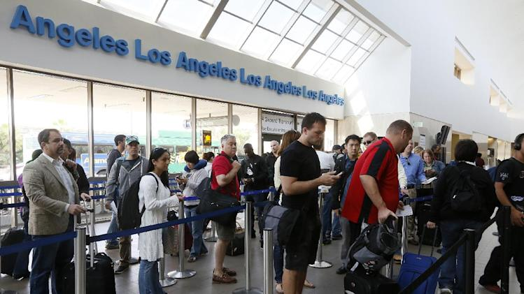 FILE - This April 22, 2013 file photo shows travelers standing in line at the LAX International Airport in Los Angeles. Under pressure, the White House signaled Wednesday it might accept legislation eliminating Federal Aviation Administration furloughs blamed for lengthy flight delays for airline passengers, while leaving the rest of $85 billion in across-the-board spending cuts in place. (AP Photo/Damian Dovarganes, File)