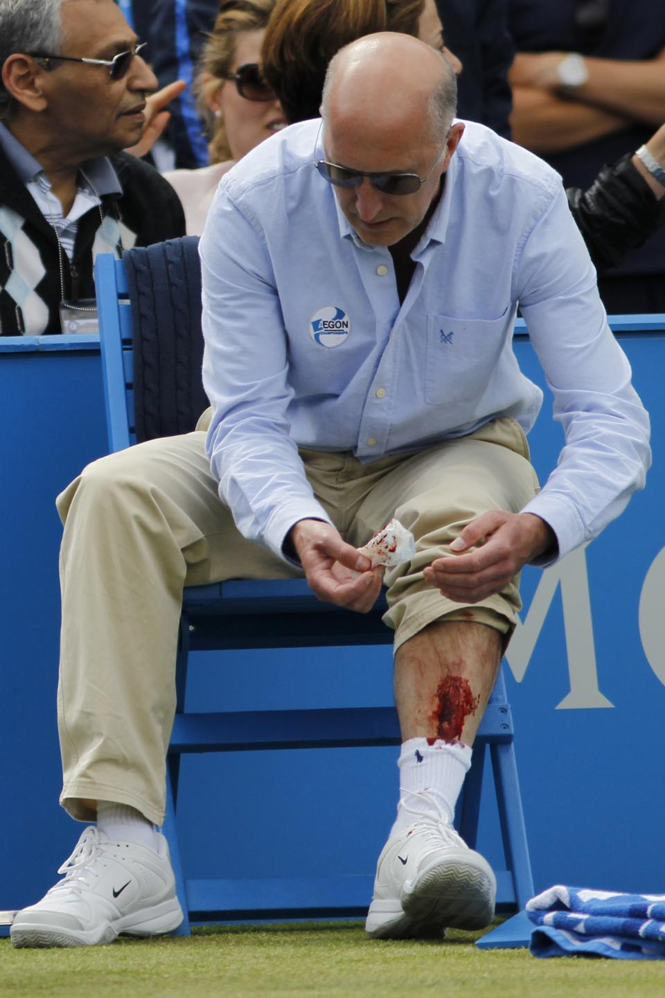 A line judge wipes blood from his injured leg after Argentina's David Nalbandian kicked a small barrier surrounding the judge, leading to his disqualification during the Queen's Club grass court championships final tennis match against Croatia's Marin Cilic, London, Sunday, June 17, 2012. (AP Photo/Sang Tan)