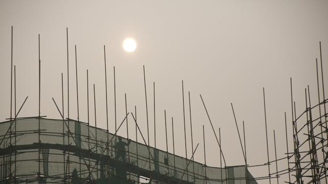A man works on a construction site of a new commercial building during a heavily polluted day in Beijing