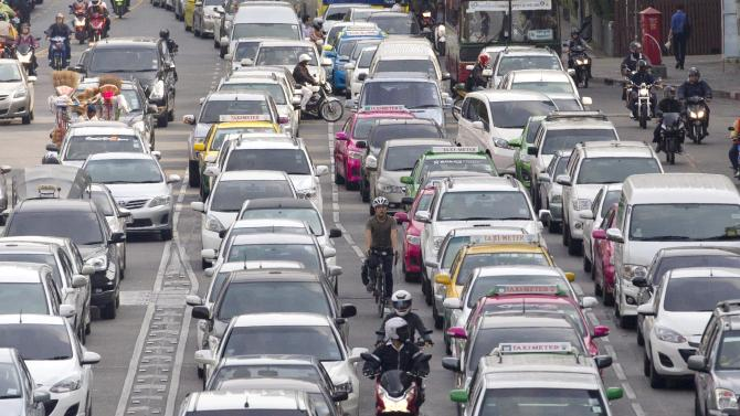 In this photo taken on March 21, 2013, Sutham Thamrongvit, riding a bicycle at center, weaves through heavy traffic during the morning rush hour in Bangkok, Thailand. Bicycling has long been almost nonexistent in this city of 10 million, where those who dare to pedal must cope with unfriendly road designs, crumbling pavement, sweltering heat and growing hordes of cars, buses and motorcycles. Yet bicycling is making early signs of a comeback. There has been some government encouragement, including a new project that allows people to borrow city-owned bikes from 50 stations scattered across the central business district. But Bangkok's traffic failures may be the greatest incentive: When cars are at a rush-hour standstill, bicycles are sometimes the only vehicles capable of moving. (AP Photo/Sakchai Lalit)
