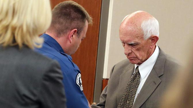 Former Arapahoe County Sheriff Patrick Sullivan, right, is handcuffed by police following his sentencing hearing for probation violation, at the Arapahoe County Justice Center, in Centennial, Colo., on Thursday, June 19, 2014. The former Colorado sheriff has been sentenced to 15 months in prison for repeatedly violating his probation in a meth-for-sex case. (AP Photo/Brennan Linsley)