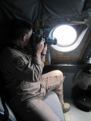 In this Jan. 25, 2013 photo, a detection officer with U.S. Customs and Border Protection takes photos of a potential drug-carrying boat from inside a P3 Orion Airborne Early Warning Aircraft while flying over waters near the Pacific coast of Costa Rica. The Central American country abolished its army in 1948 and plowed money into education, social benefits and environmental preservation. As a result, Costa Rican officials say, the country can't battle ruthless and well-equipped Mexican drug cartels without U.S. help. The U.S. is patrolling Costa Rica's skies and waters and providing millions of dollars in training and equipment to Costa Rican officials who have launched a tough line on crime backed by top-to-bottom transformation of the law-enforcement and justice systems. (AP Photo/Michael Weissenstein)