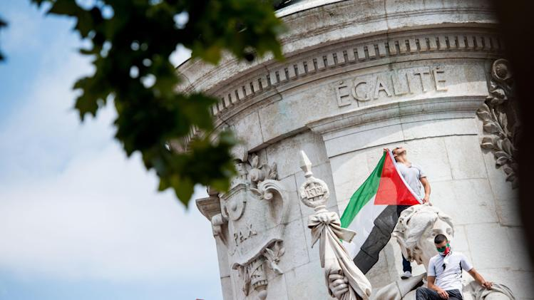 A pro-Palestinian protester displays a Palestinian flag while standing on a monument at Place de la Republique in Paris, France, during a banned demonstration in support of Gaza, Saturday, July 26, 2014. French police fired tear gas as clashes broke out at a banned pro-Gaza demonstration on Saturday as thousands defied a ban on the protest. The interior minister had earlier called on organizers of the Paris demonstration to observe the ban imposed to halt potential anti-Semitic violence. (AP Photo/Benjamin Girette)