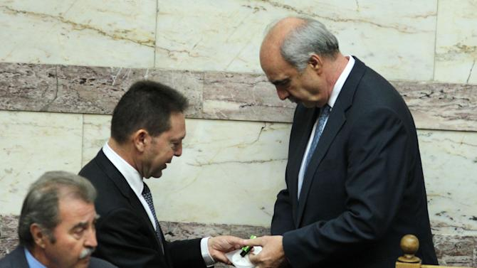 Greece's Finance Minister Yannis Stournaras, left, gives a disc containing the new draft state budget for 2013 to Parliament speaker Evangelos Meimarakis, right, at the Greek parliament  in Athens, Wednesday, Oct. 31, 2012. Greek lawmakers are to vote Wednesday on a privatization bill that will be the first major test for the country's troubled governing coalition, while journalists have walked off the job at the start of rolling 24-hour strikes to protest austerity plans that will affect their healthcare funds. (AP Photo/Thanassis Stavrakis)