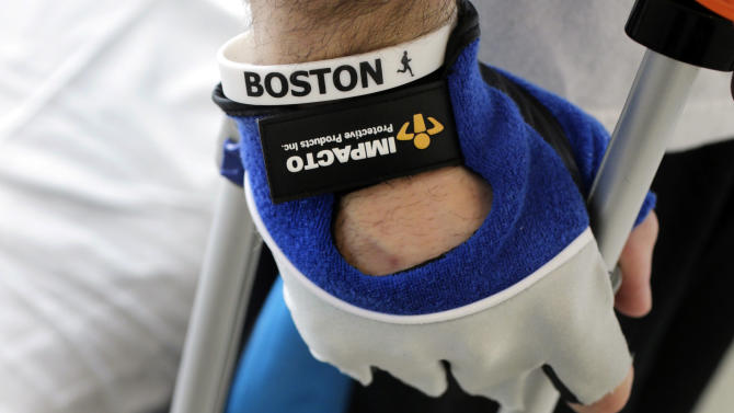 """In this Wednesday, May 22, 2013 photo, Boston Marathon bombing survivor Pete DiMartino, of Rochester, N.Y., wears a Boston wristband following a physical therapy session at the Spaulding Rehabilitation Hospital in Boston. DiMartino was injured in an explosion near the finish line, which blew away much of one leg and burned the other. """"I don't want anybody feeling sorry for me,"""" he said. """"... I want people to see that this has made me a better person and I want people to become better people through what they see through me."""" (AP Photo/Charles Krupa)"""
