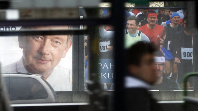 Electoral posters of president incumbent, Danilo Turk, left and former prime minister Borut Pahor are seen through a bus window in Ljubljana, Slovenia, Friday, Nov. 30, 2012. Runoff for presidential elections will be held on Sunday, Dec. 2, 2012. (AP Photo/Matej Leskovsek)