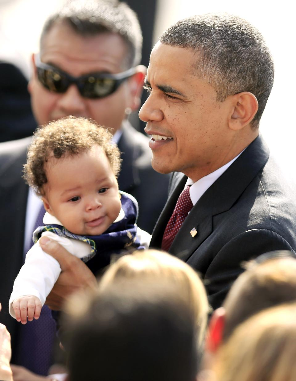 President Barack Obama holds 4-month-old Milan Maxey Young of Boston after arriving in Manchester, N.H. for a campaign stop Saturday, Oct. 27, 2012. (AP Photo/Winslow Townson)