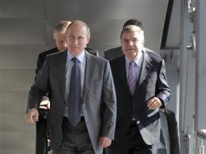 Russia's President Vladimir Putin and International Olympic Committee (IOC) President Thomas Bach walk during the opening of a railway station in Adler district in Sochi