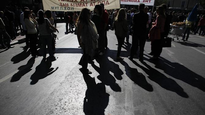 Journalists cast their shadows on the road during a protest, in Athens Wednesday, Oct. 31 2012. Greece's two main labor unions covering civil servants and the private sector have called a 48-hour strike to protest austerity measures due to be voted on next week. The strike call came as the finance minister submitted an amended 2013 budget that raised the country's debt and deficit forecasts for next year. (AP Photo/Kostas Tsironis)