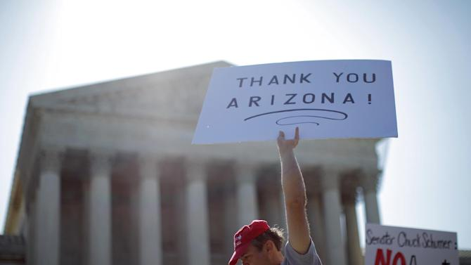 """A supporter of Arizona's """"show me your papers"""" immigration law, who declined to be identified, demonstrates in front of the Supreme Court in Washington, Wednesday, April 25, 2012. (AP Photo/Charles Dharapak)"""