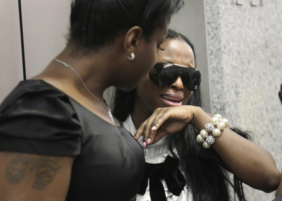 Inga Marchand, also known as Foxy Brown, right, becomes emotional after leaving the courtroom in New York, Tuesday, July 12, 2011. Charges that rapper Foxy Brown violated a court order by mooning her neighbor have been dropped. (AP Photo/Seth Wenig)
