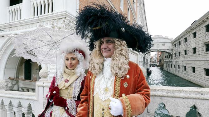 Revellers pose in front of the Ponte dei Sospiri (Bridge of Sighs) during the first day of the Venice Carnival