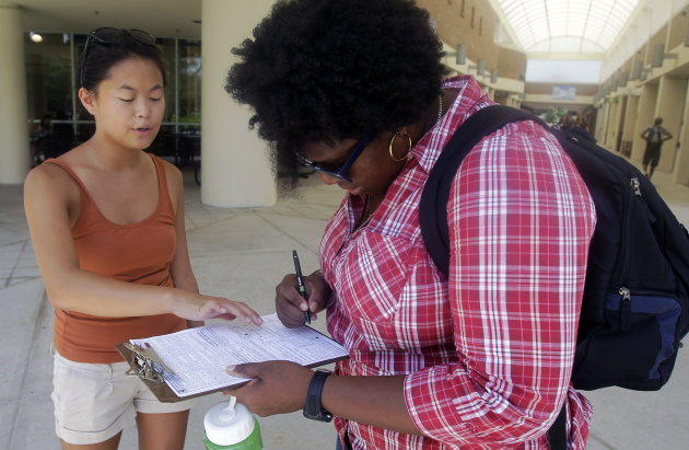 In this Tuesday, July 31, 2012, photo, Aubrey Marks, left, helps a University of Central Florida student to register to vote in Orlando, Fla. While most college campuses are relatively quiet, students at the University of Central Florida have taken it upon themselves to register their peers during the summer. Gone are the days when young voters weren't taken seriously. In 2008, they helped propel Barack Obama into the Oval Office, supporting him by a 2-1 margin. But that higher profile also has landed them in the middle of the debate over some state laws that regulate voter registration and how people identify themselves at the polls. (AP Photo/John Raoux)
