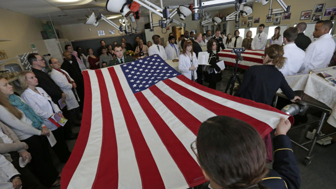 In this photo taken Friday, Jan. 25, 2013, in Gary, Ind., A military honor guard folds the flag of a Viet Nam veteran and anonymous donor, during a memorial service for bodies donated to science at Indiana University School of Medicine - Northwest. During the hour long service, relatives of donors gather around the steel tables where their loved ones were dissected along with the medical students who worked on the bodies during the previous semester. The students read letters of appreciation, clergy offer prayers, and tears are shed. The program is geared towards teaching the medical students that this is not merely a cadaver, but a person, and their first patient. (AP Photo/M. Spencer Green)
