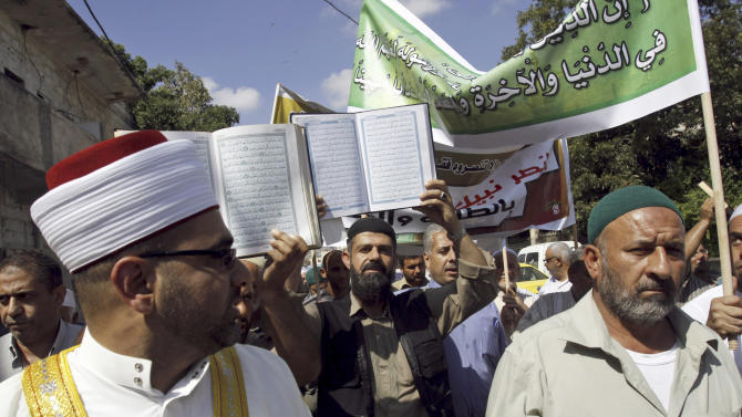 """Palestinian protesters hold copies of the Quran, the Muslim holy book, during a protest against the movie """"Innocence of Muslims"""", in the West Bank town of Jenin, Thursday, Sept. 20, 2012, as part of widespread anger across the Muslim world about a film ridiculing Islam's Prophet Muhammad.(AP Photo/Mohammed Ballas)"""