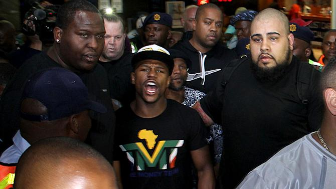 """Boxer Floyd Mayweather Jr, center, on his arrival in Johannesburg Wednesday Jan 15, 2014. Mayweather Jr. is in the country for a six-day visit that the government hopes will help """"resuscitate"""" boxing in the country. (AP Photo)"""