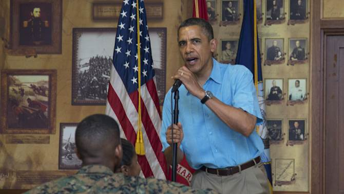 President Barack Obama speaks as he and first lady Michelle Obama, not seen, arrive to visit with members of the military and their families in Anderson Hall at Marine Corp Base Hawaii, Tuesday, Dec. 25, 2012, in Kaneohe Bay, Hawaii. The first family is in Hawaii for a holiday vacation. (AP Photo/Carolyn Kaster)