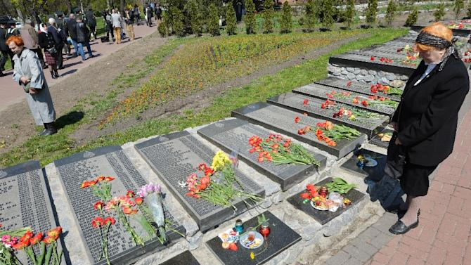 An elderly woman pays her respects to the victims of the Chernobyl nuclear disaster at a memorial in Kiev on April 26, 2015