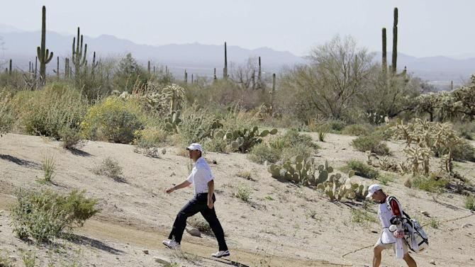 Lee Westwood, of England, walks through the rough along the sixth fairway while playing Nick Watney during the Match Play Championship golf tournament, Friday, Feb. 24, 2012, in Marana, Ariz. (AP Photo/Eric Risberg)