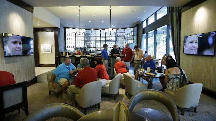 """In this July 3, 2013, photo, guests socialize in the newly-redesigned bar area during """"social hour"""" at a Sheraton hotel in Seattle. Long treated as dead spaces that hotel guests raced through on the way to the elevator, lobbies are being transformed into places to work, surf the Web or meet friends for a drink. (AP Photo/Elaine Thompson)"""