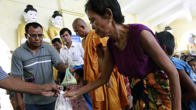 A woman receives bags of rice provided by private donors as she and others take refuge in a monastery compound in Sittwe, the capital of Rakhine state in western Myanmar, where sectarian violence continues to impact the public, Wednesday, June 13, 2012. Heavy rain Wednesday brought an uneasy calm to western Myanmar after five days of deadly sectarian strife, though residents said they were too afraid to sleep at night and faced food shortages. (AP Photo/Khin Maung Win)