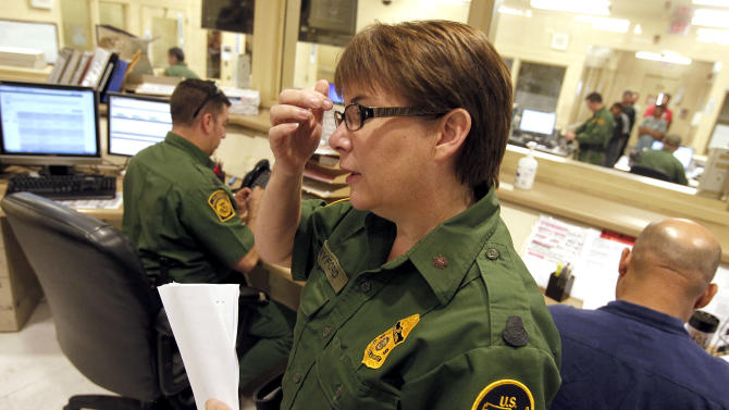 U.S. Border Patrol Tucson Sector Branch Chief Donna Twyford examines an illegal immigrant's file as they are  processed at Tucson Sector U.S. Border Patrol Headquarters Thursday, Aug. 9, 2012, in Tucson, Ariz.  The U.S. government has halted flights home for Mexicans caught entering the country illegally in the deadly summer heat of Arizona's deserts, a money-saving move that ends a seven-year experiment that cost taxpayers nearly $100 million.(AP Photo/Ross D. Franklin)