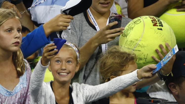 A girl smiles from the crowd after receiving the wristband of Eugenie Bouchard of Canada, after she defeated Barbora Zahlavova Strycova of the Czech Republic in their women's singles match at the 2014 U.S. Open tennis tournament in New York