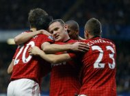 Manchester United&#39;s players, Wayne Rooney, centre, celebrate, after Chelsea scored an own goal, during their English Premier League soccer match, at Stamford Bridge Stadium in London, Sunday, Oct. 28, 2012. (AP Photo/Kirsty Wigglesworth)
