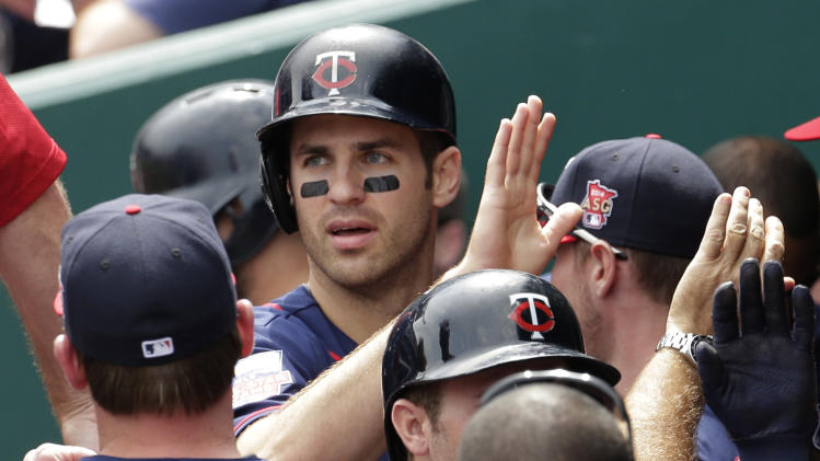 Minnesota Twins' Joe Mauer, top, celebrates with teammates in the dugout after scoring on a double by Trevor Plouffe during the first inning of a baseball game against the Kansas City Royals, Sunday, April 20, 2014, at Kauffman Stadium in Kansas City, Mo. (AP Photo/Charlie Riedel)