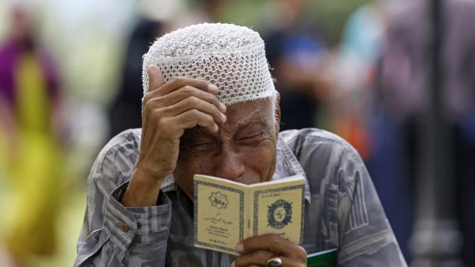 An Acehnese man cries while praying for a tsunami victim at a mass graveyard in Banda Aceh