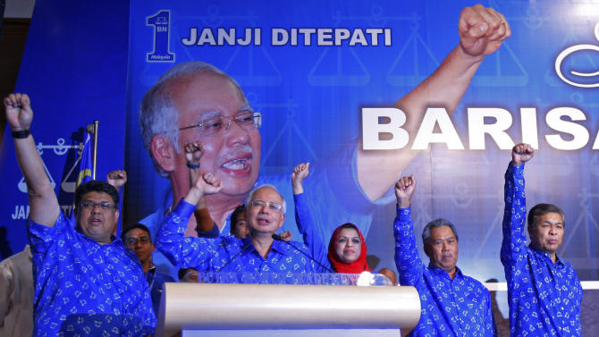 Malaysian Prime Minister Najib Razak, second from left, and his other party leaders shout slogans after winning the national elections in Kuala Lumpur, Malaysia, early Monday, May 6, 2013. Malaysia's long-governing coalition won national elections Sunday to extend its 56 years of unbroken rule, fending off the strongest opposition it has ever faced but exposing vulnerabilities in the process. (AP Photo/Lai Seng Sin)