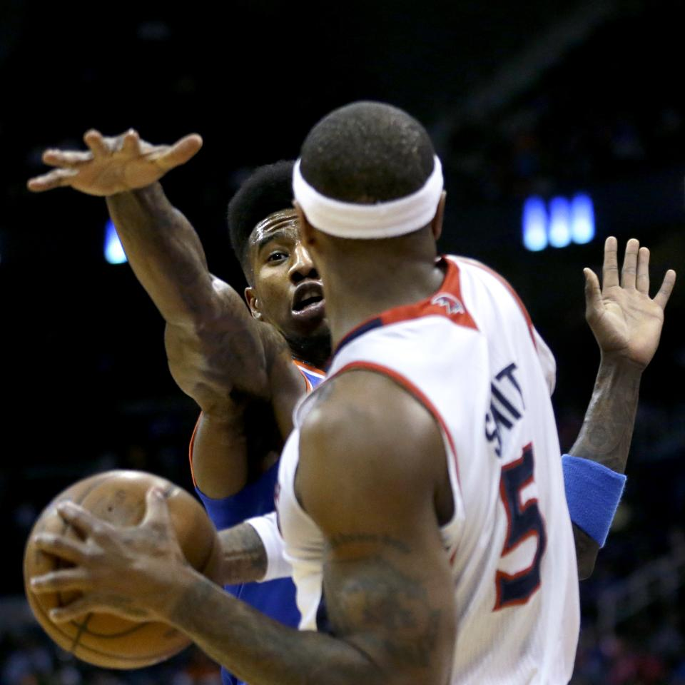 New York Knicks' Iman Shumpert, left, reaches for the ball held by Atlanta Hawks' Josh Smith in the first quarter of an NBA basketball game, Wednesday, April 3, 2013, in Atlanta. (AP Photo/David Goldman)