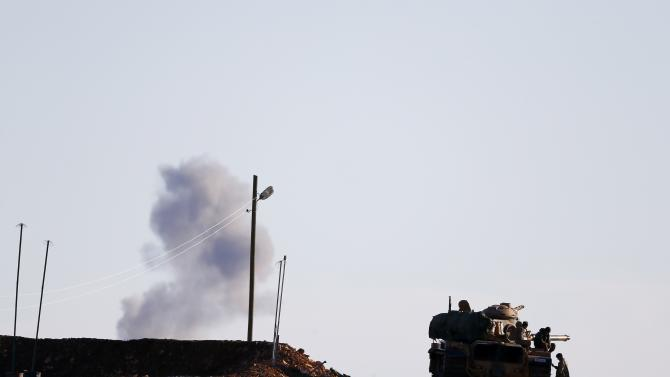 A Turkish army tank drives near the Mursitpinar crossing on the Turkish-Syrian border as smoke rises in the background from the Syrian town of Kobani