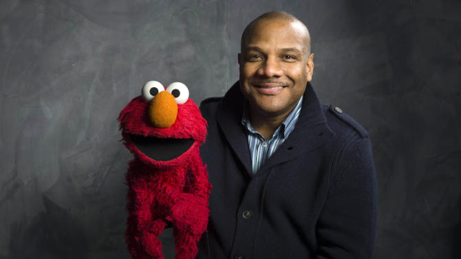 "FILE - In this Jan. 24, 2011 file photo, Elmo puppeteer Kevin Clash poses with the ""Sesame Street"" muppet in the Fender Music Lodge during the 2011 Sundance Film Festival in Park City, Utah. (AP Photo/Victoria Will, File)"