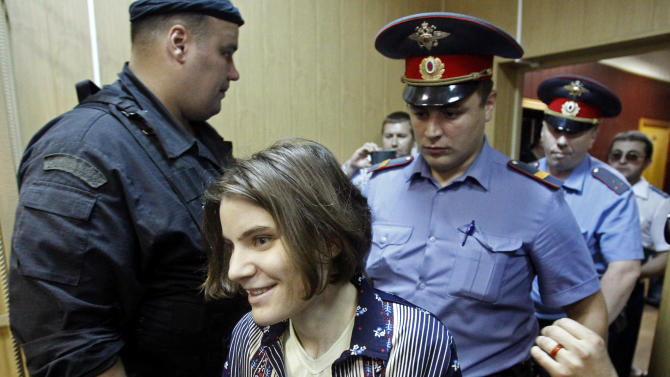 """Yekaterina Samutsevich, a member of the feminist punk band, Pussy Riot, is escorted in a district court in Moscow, Wednesday, June 20, 2012. She and two other band members face up to seven years on hooliganism charges after their February """"punk prayer"""" at Moscow's Christ the Savior Cathedral in which they asked Holy Mary to deliver Russia from President Vladimir Putin.(AP Photo/Misha Japaridze)"""