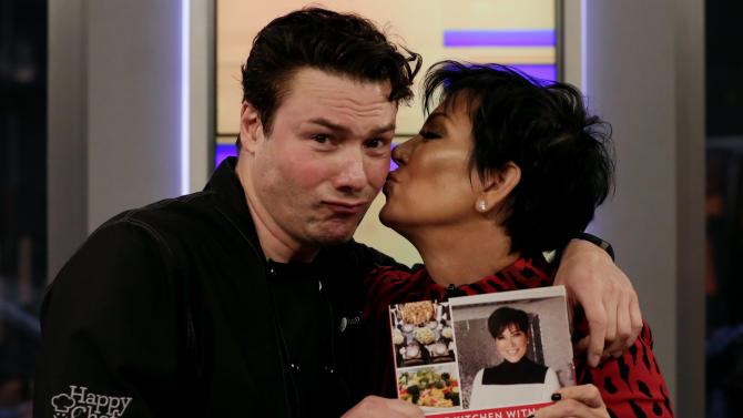 """Kris Jenner poses for a photo with chef Rocco DiSpirito after she prepared a recipe from her cookbook """"In the Kitchen With Kris: A Kollection of Kardashian-Jenner Family Favorites,"""" on the """"Fox & friends"""" television program in New York Tuesday, Oct. 21, 2014. (AP Photo/Richard Drew)"""
