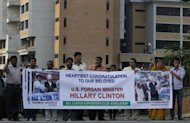 Supporters of US Secretary of State Hillary Clinton line the streets as her motorcade makes its way through the streets of Dhaka, Bangladesh. Clinton was to use a rare visit to Bangladesh Sunday to throw her support behind Muhammad Yunus, the microfinance pioneer and Nobel laureate who has clashed with the state